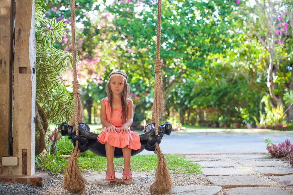 beautiful-little-girl-swinging-on-a-swing-in-a-cozy-lovely-flowered-courtyard