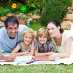 happy-family-painting-in-a-park-smiling-at-the-camera