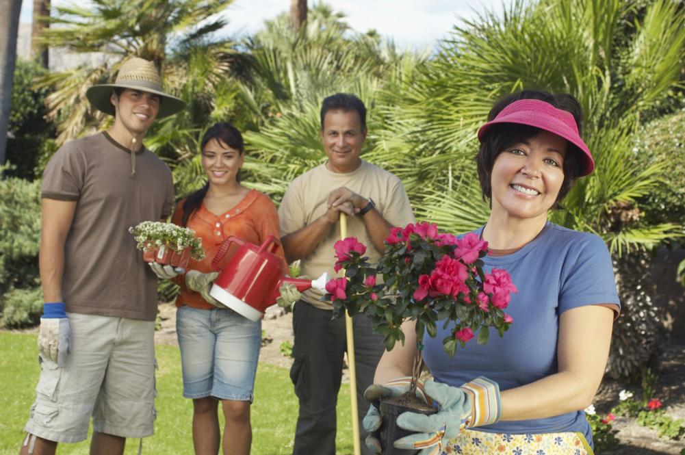 portrait-of-a-happy-woman-holding-flower-plant-with-family-standing-in-the-background