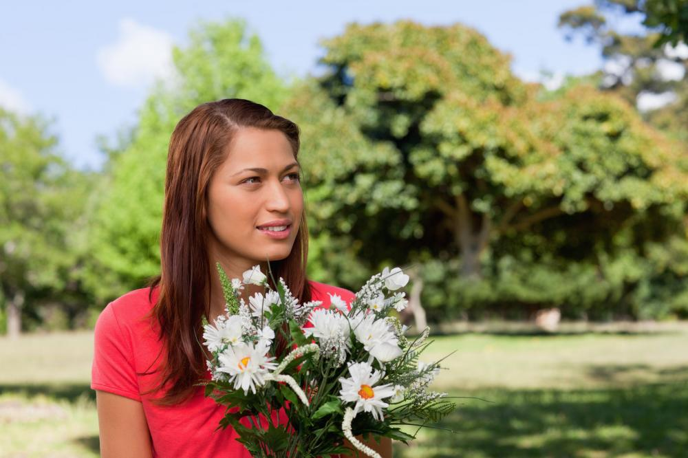 young-woman-looking-towards-the-side-while-holding-a-bunch-of-fl